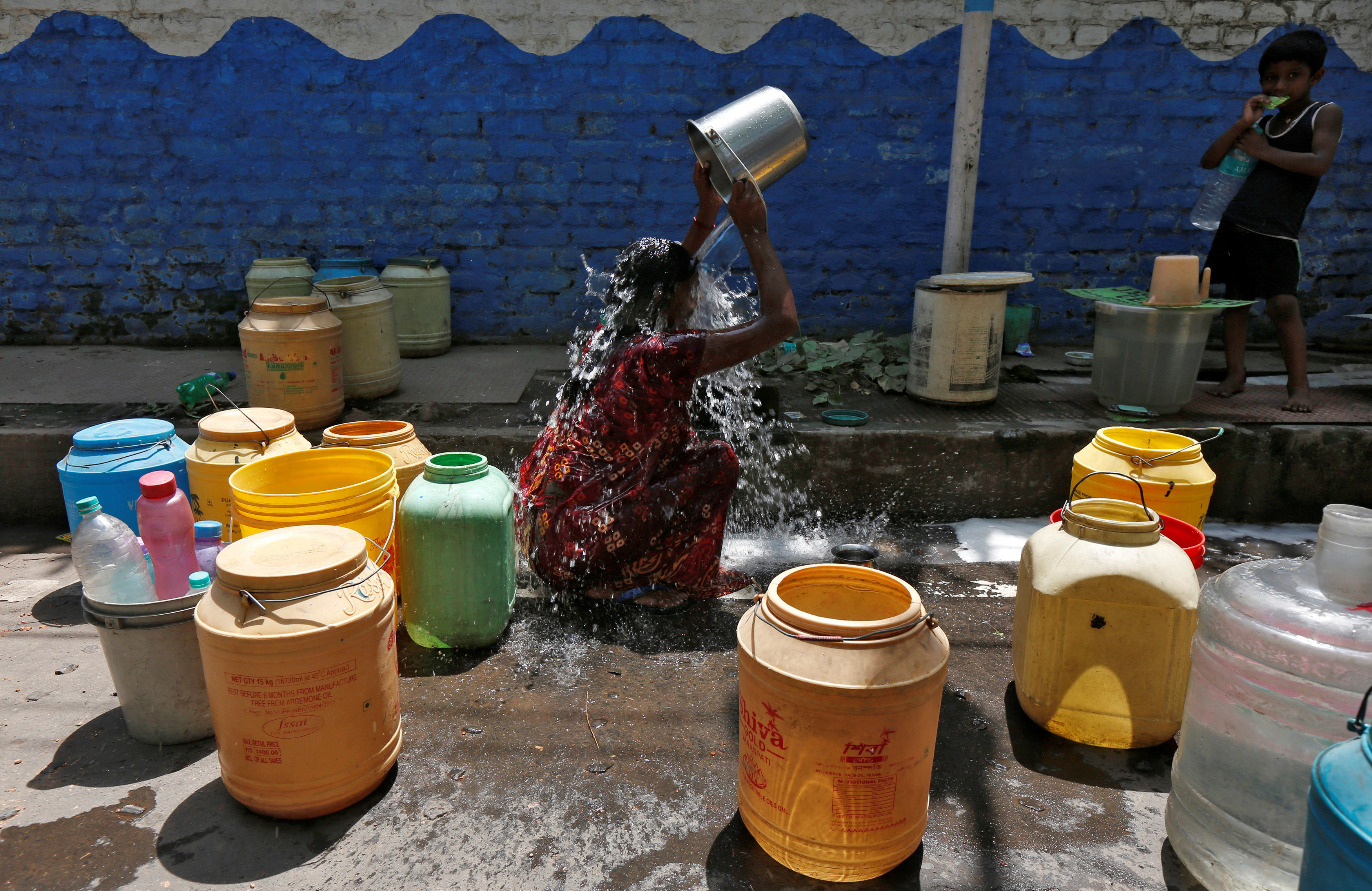 A woman bathes at a roadside municipal tap in a slum area on a hot summer day on the outskirts of Kolkata