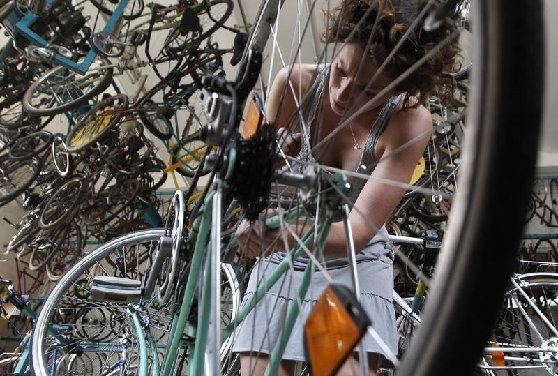 A woman repairs a bike at a bicycle workshop