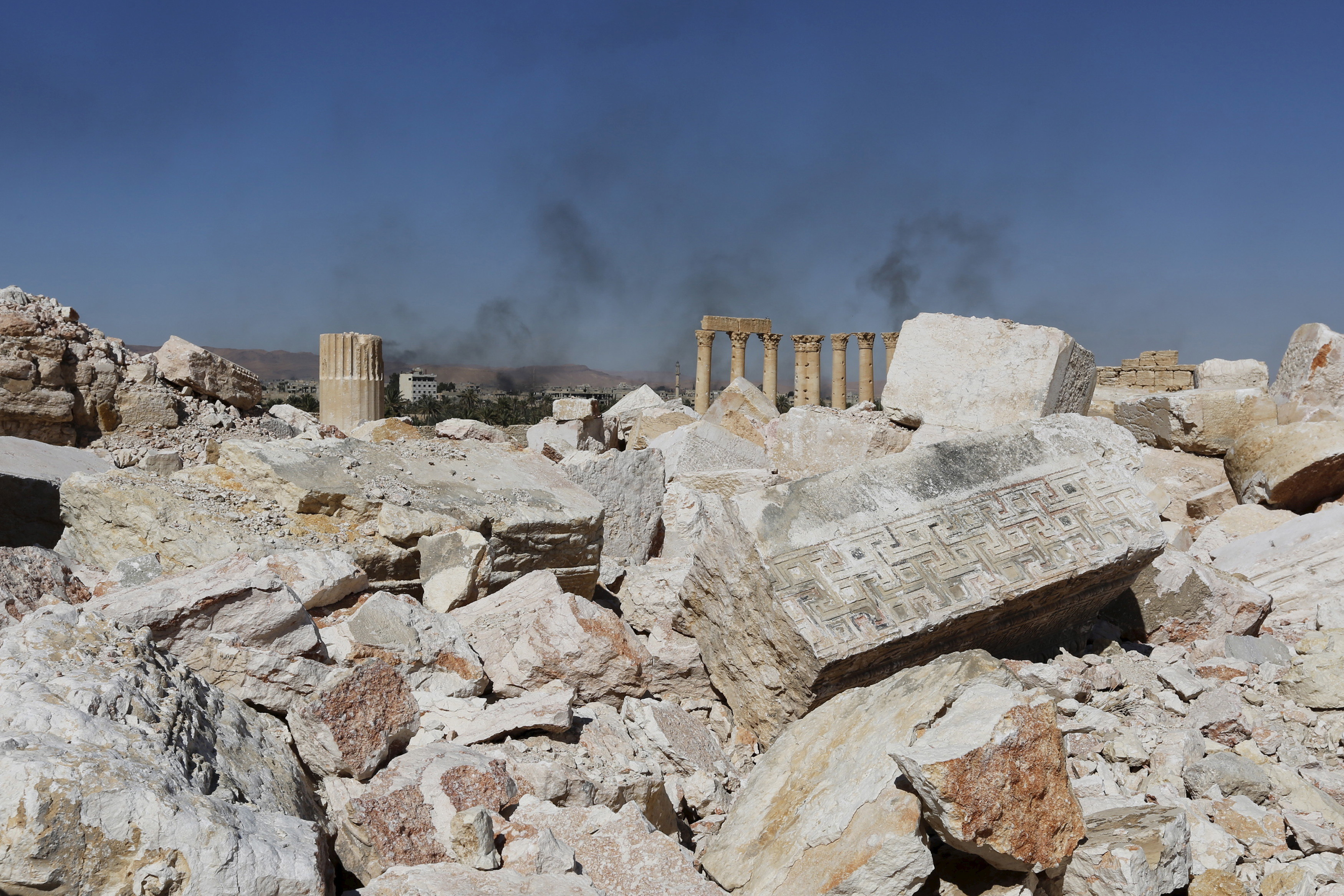 Smoke rises from the modern city as seen from the historic city of Palmyra, in Homs Governorate, Syria