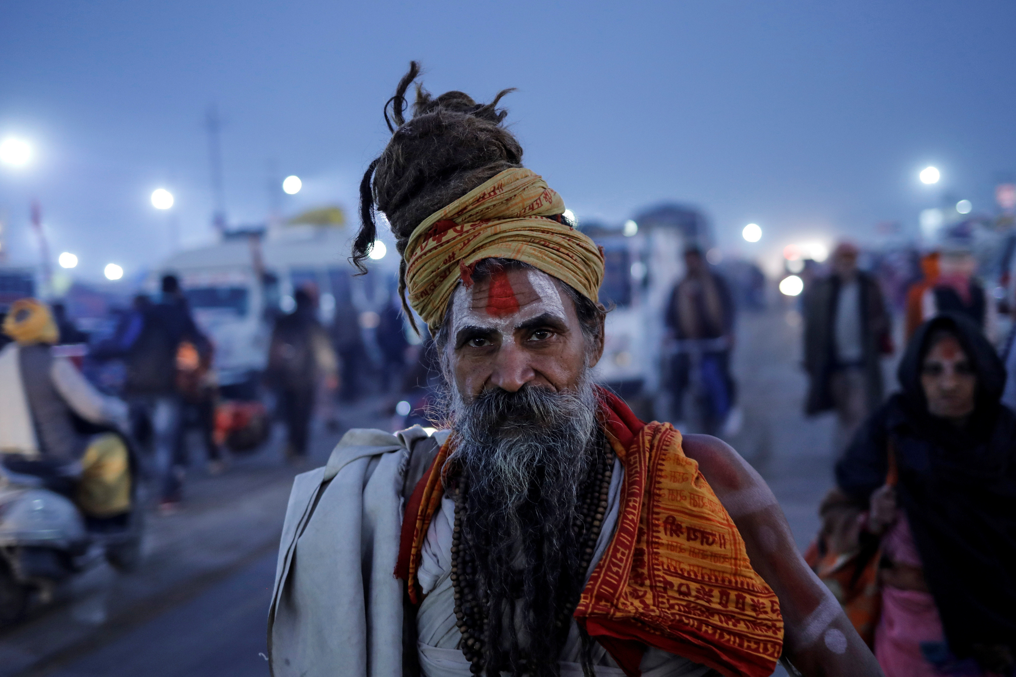 A Sadhu or a Hindu holy man walks on a road at the site of the