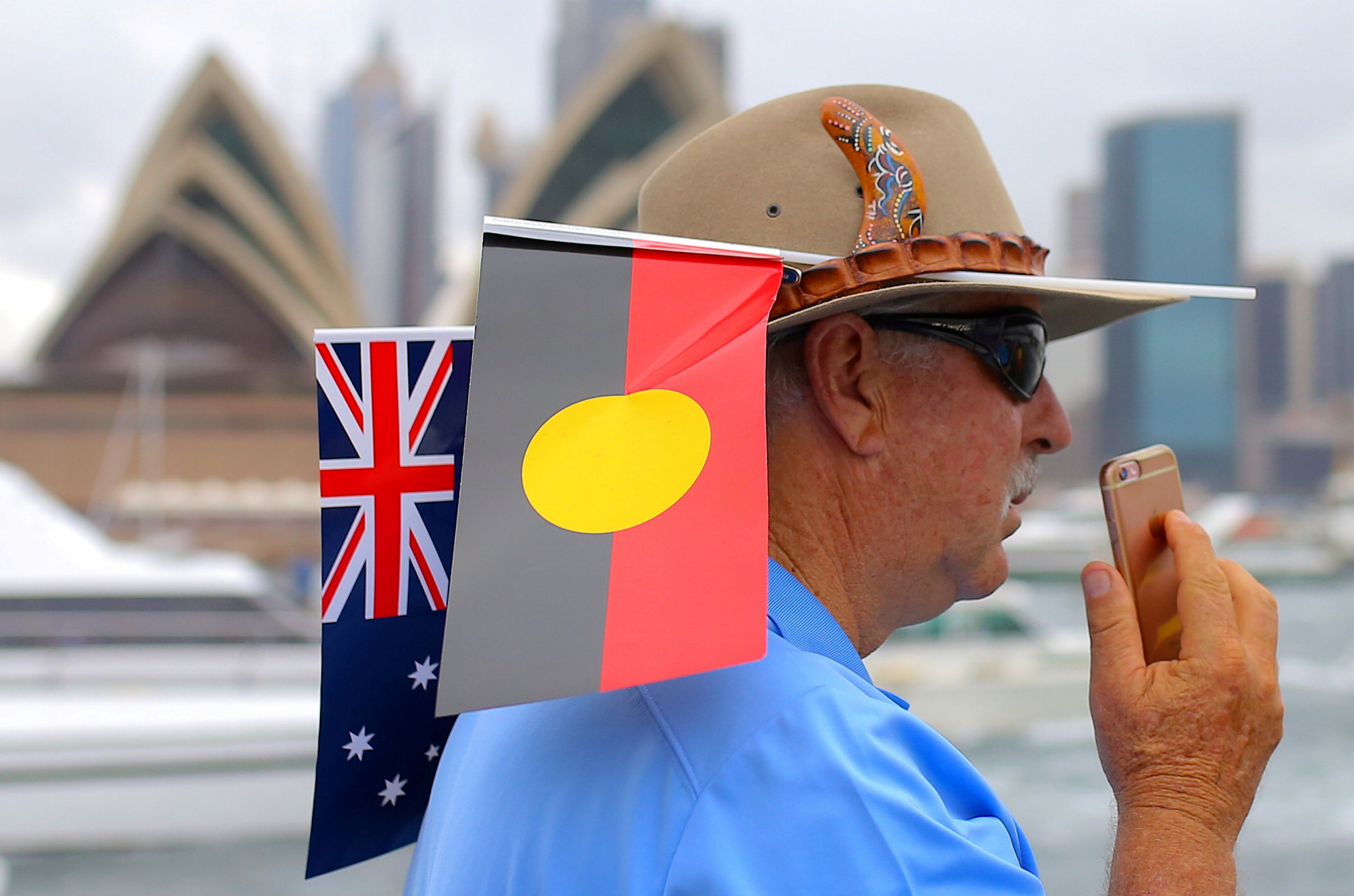 A passenger aboard a ferry wears an Australian Aboriginal flag and national flag in his hat as the talks on his phone during celebrations for Australia Day, which marks the arrival of Britain's First Fleet in 1788, on Sydney Harbour in Australia, January 26, 2018.   REUTERS/Steven Saphore - RC1ABF3A1480