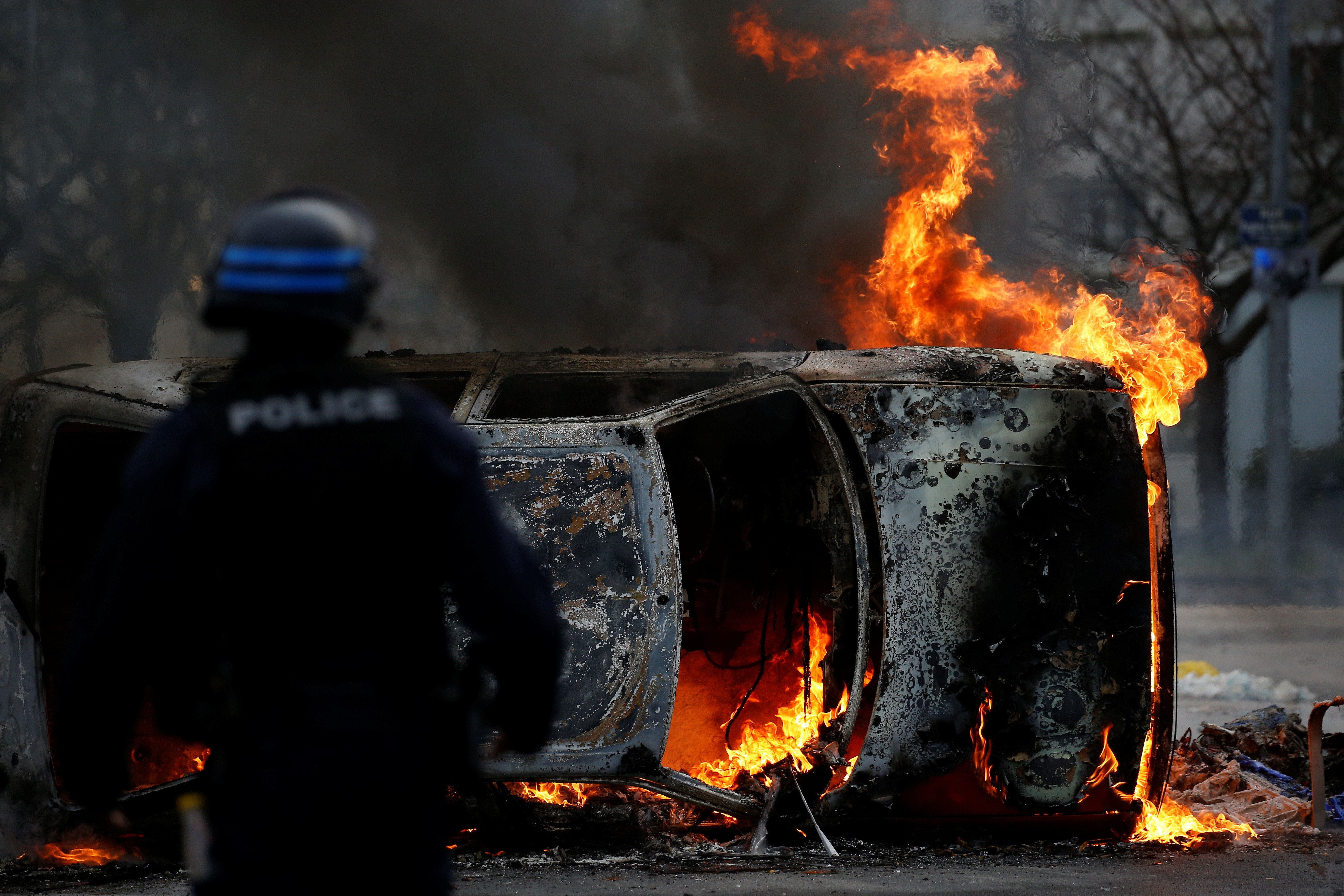 A French riot policeman stands next to a burning car as youth and high school students protest against the French government's reform plan, in Nantes, France, December 6, 2018. REUTERS/Stephane Mahe - RC1C04372080