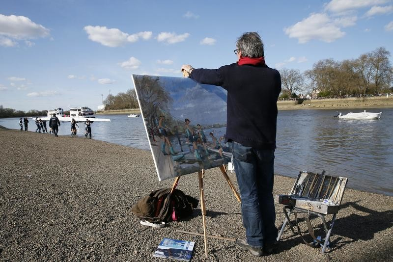 An artist paints the Cambridge crew as the Oxford crew prepare to take to the water on the banks of the Thames ahead of the Oxford versus Cambridge University boat race in London, April 11, 2015. REUTERS/Stefan Wermuth - LR2EB4B1714P0