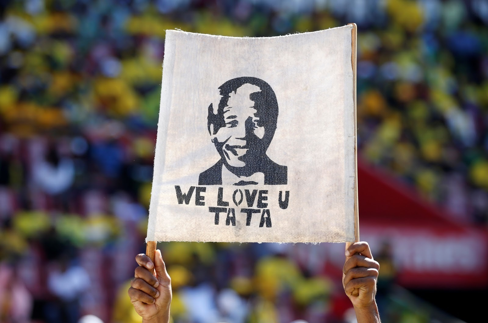 A supporter holds a placard with the face of the late Nelson Mandela, former President of South Africa, during the party's final rally at Ellis Park Stadium stadium in Johannesburg, South Africa, May 5, 2019. REUTERS/Siphiwe Sibeko - RC1B4D73C0F0