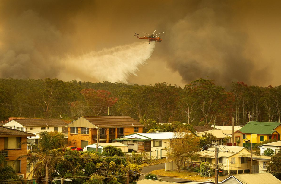 An Air-crane water bombing helicopter drops water on a bush fire in Harrington.
