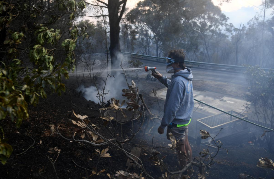 A resident hoses smouldering logs as a bushfire burns in Woodford NSW, Australia, November 8th, 2019.