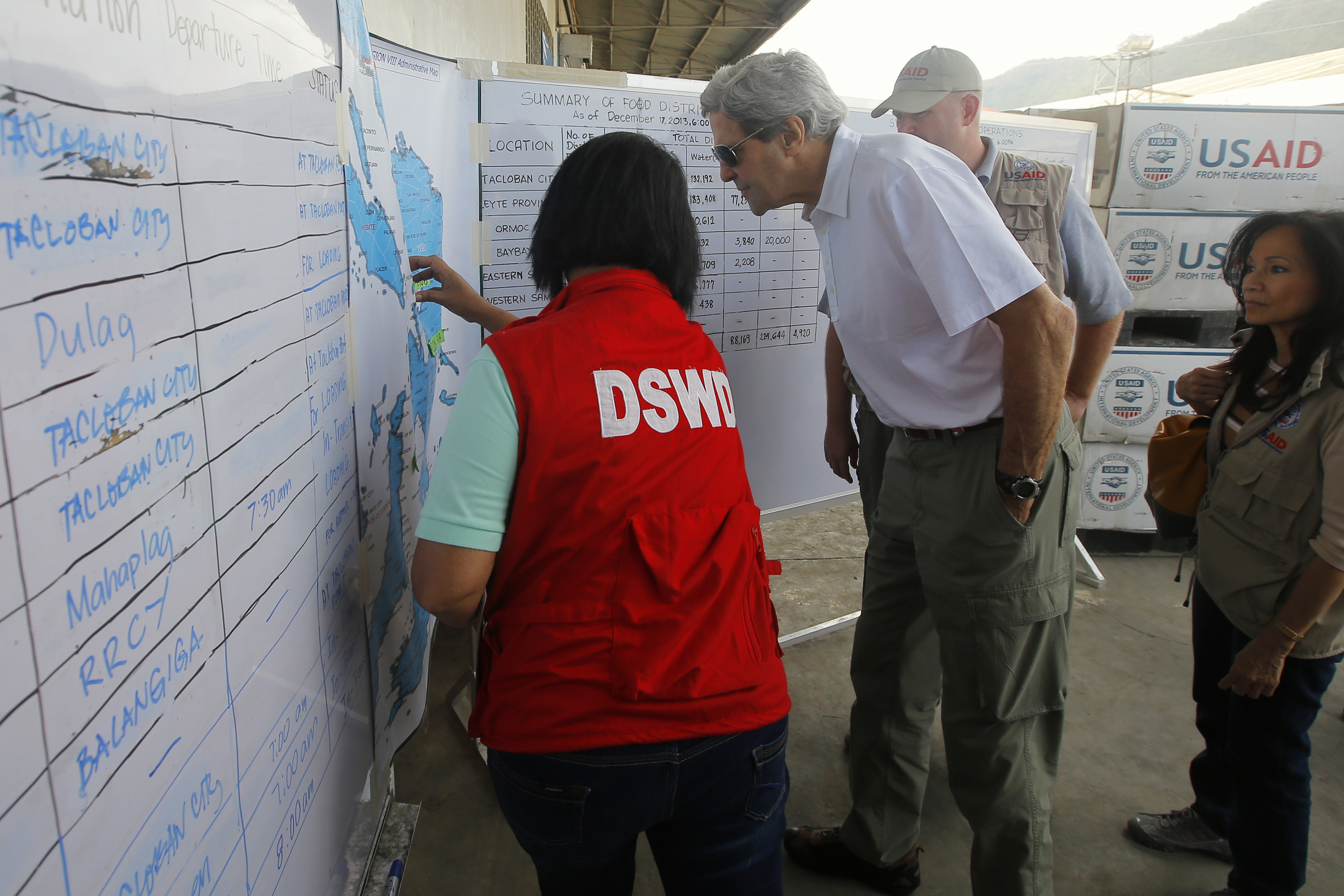 U.S. Secretary of State John Kerry looks over a map of the area during a tour of a relief distribution center in Tacloban December 18, 2013. Kerry announced that the U.S. government, through USAID, will provide an additional nearly $25 million humanitarian aid for the survivors of super typhoon Haiyan, which decimated towns and villages around Tacloban on November 8, killing more than 6,000 people and displacing 4 million.  REUTERS/Brian Snyder   (PHILIPPINES - Tags: POLITICS DISASTER SOCIETY) - RTX16N4D