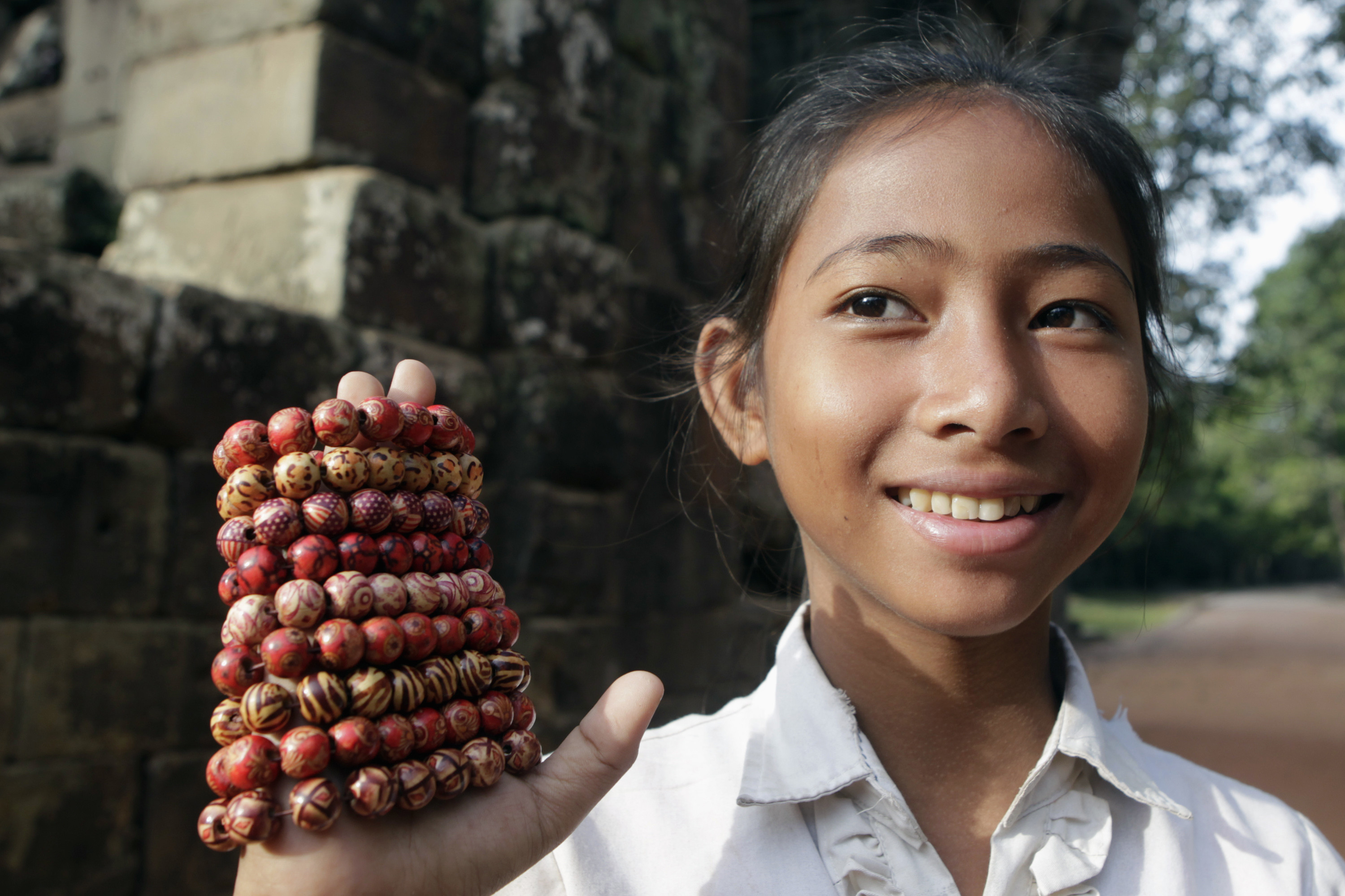 A girl sells native bracelets outside Cambodia's Ta Prohm temple in Siem Reap.