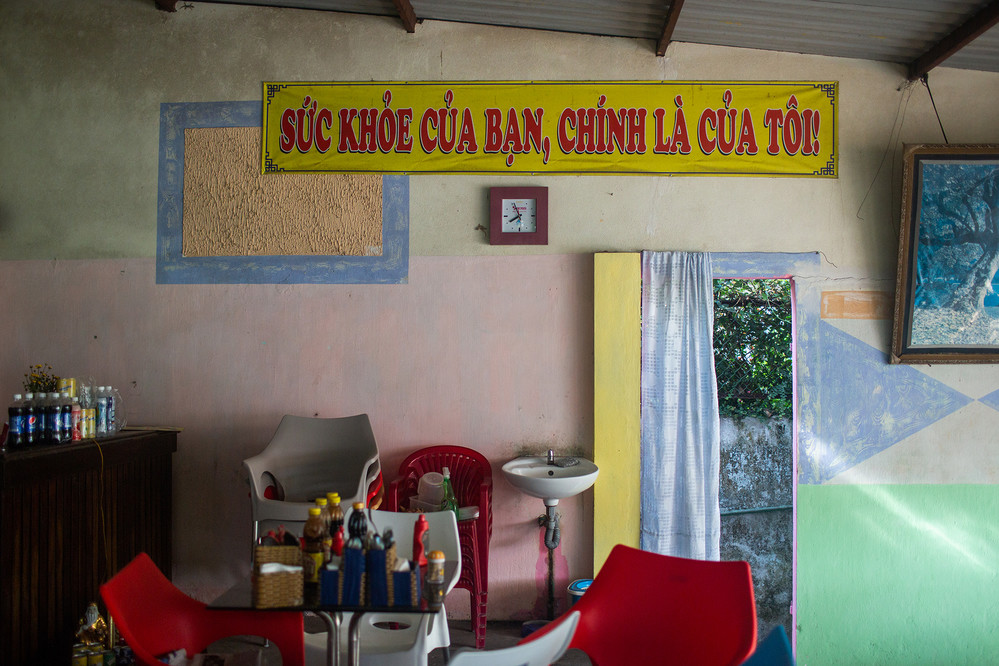 """A sign that reads """"Your Health is My Health"""" hangs in the Cafe Hua Sua on the edge of Ho Mung Lake in Hue. The lake is one of the clean-up sites proposed by the Centre for Social Research and Development."""