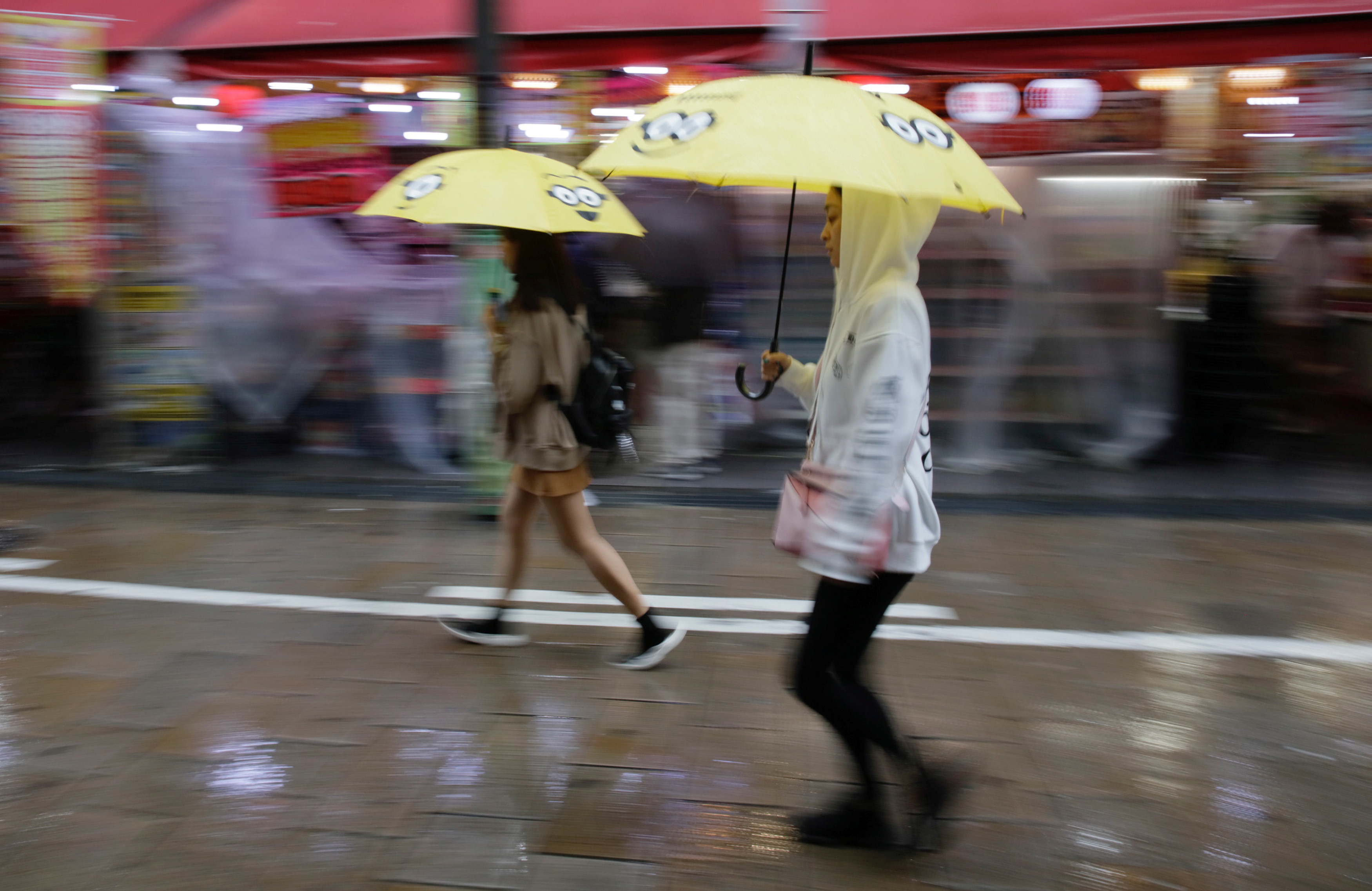 Shoppers walk under umbrellas as Typhoon Lan approaches Japan's mainland, in Osaka, western Japan, October 22, 2017. REUTERS/Thomas White - RC1BF761A190