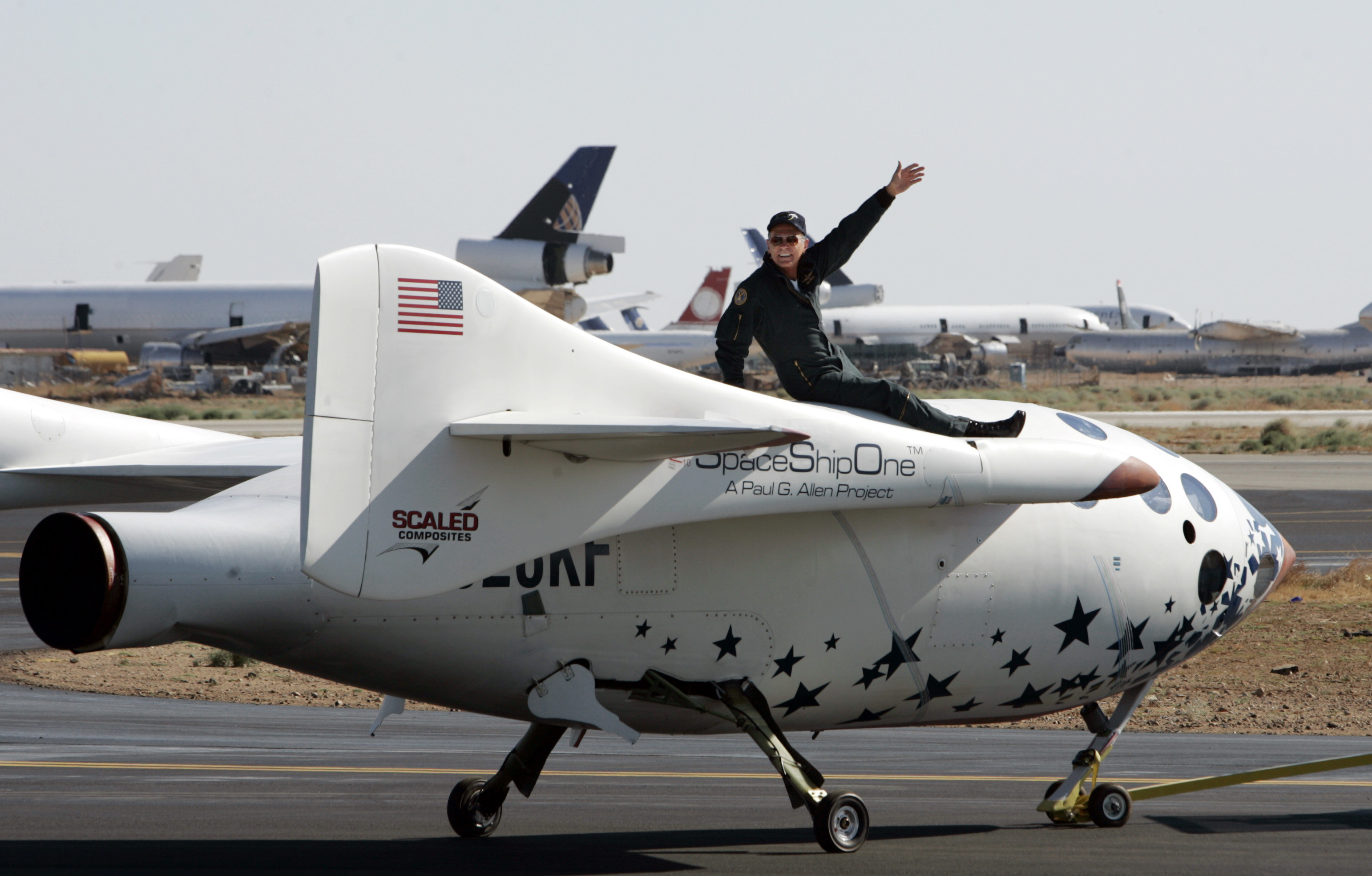 Pilot Mike Melville waves as he sits atop SpaceShipOne as it is towed following his historic flight of the world's first privately funded rocket plane beyond Earth's atmosphere at the Mojave Airport in California, June 21, 2004. SpaceShipOne, designed by legendary aerospace designer Burt Rutan and funded by billionaire Paul Allen, reached a height of 62 miles making Melville the world's first private astronaut. REUTERS/Mike Blake  MB - RTR4UJ0