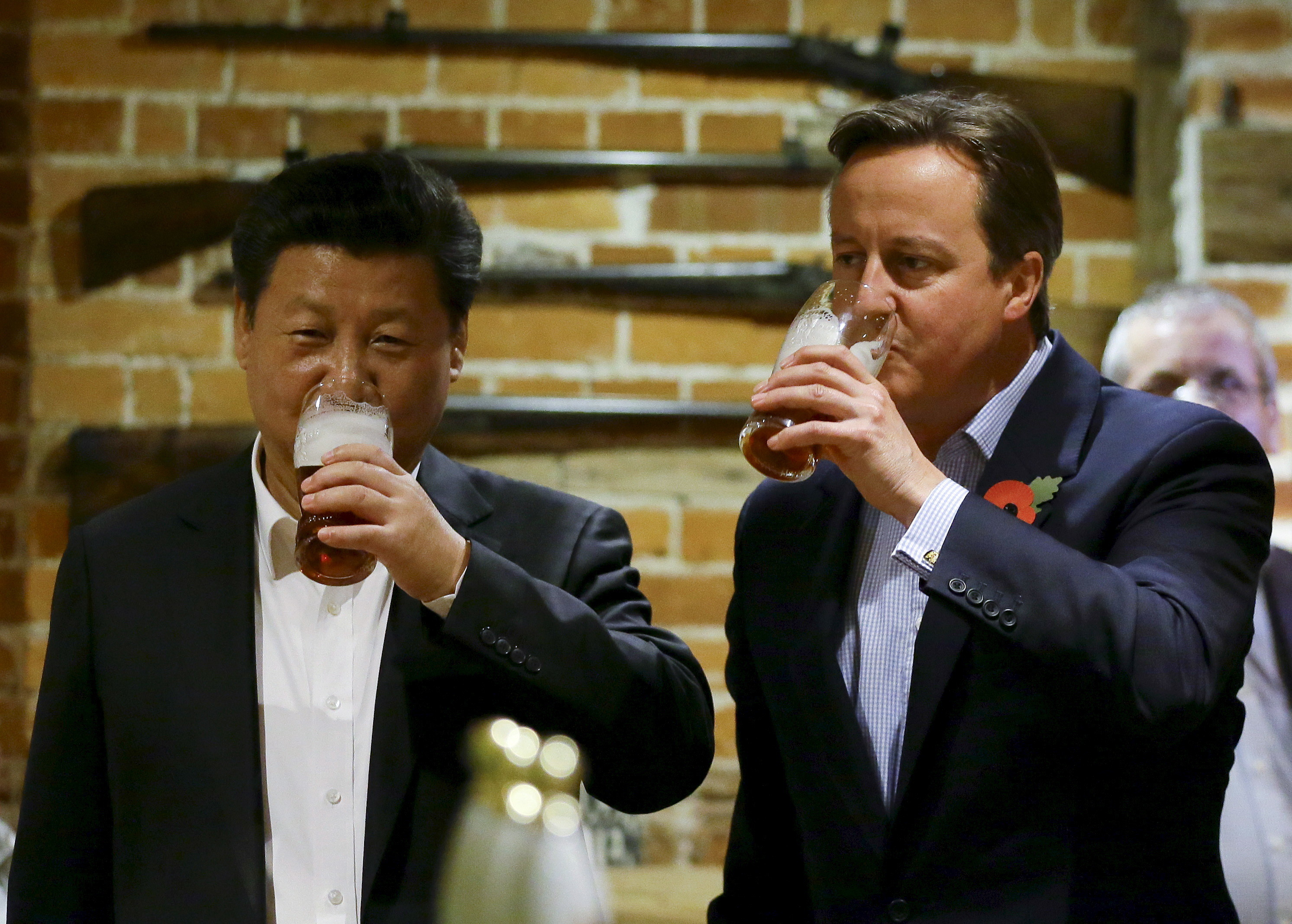 Britain's Prime Minister David Cameron (R) drinks beer with Chinese President Xi Jinping at a pub in Princes Risborough, near Chequers, England, October 22, 2015.  REUTERS/Kirsty Wigglesworth/Pool      TPX IMAGES OF THE DAY - GF20000028680