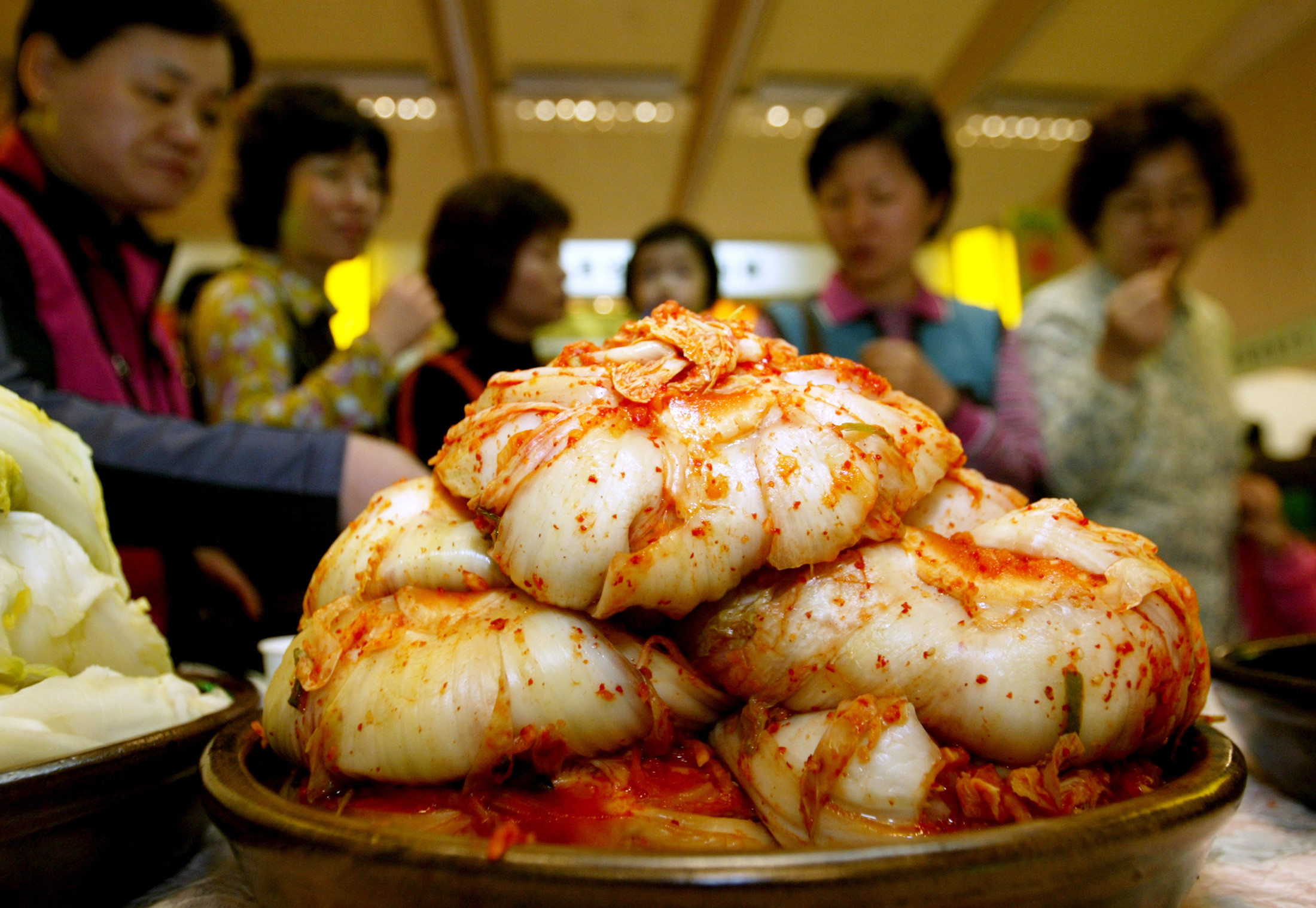 South Koreans partake in a kimchi tasting at the Kimchi Expo 2005 in Seoul, November 3, 2005. Kimchi is served at almost every meal and made in most homes. But increasing imports of the spicy cabbage from China have raised a ruckus about a foreign country eating away at the market for a national dish that is at the essence of Korean identity. For released with feature Korea-China-Kimchi. REUTERS/Kim Kyung-Hoon - RTR1AH2C