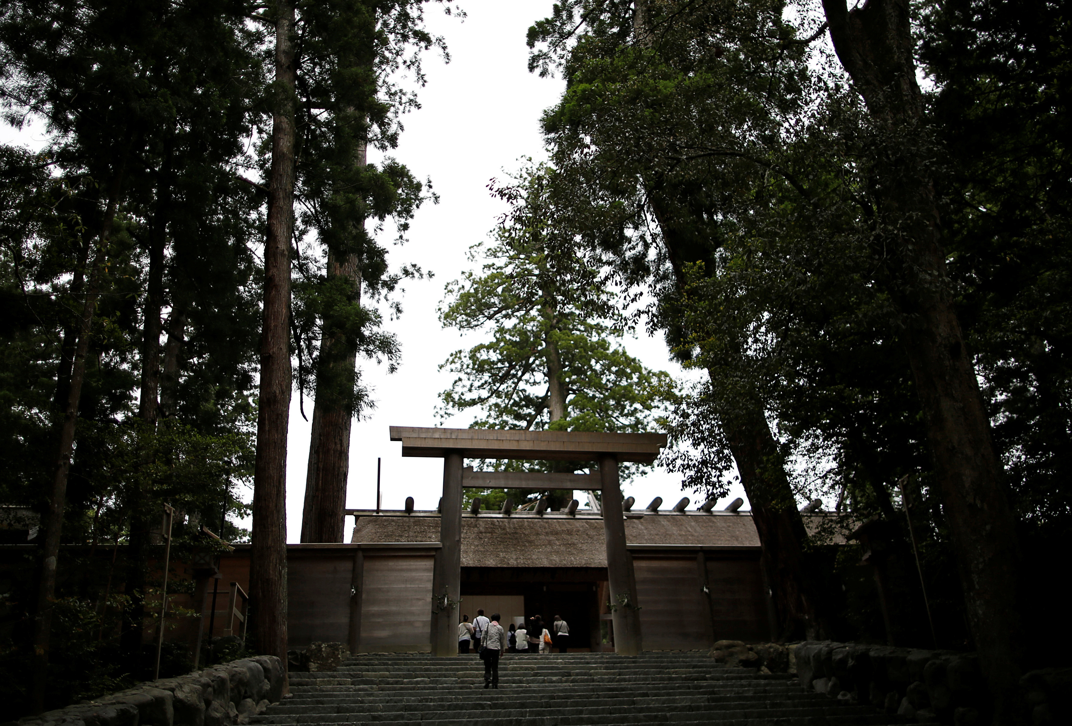 People walk through a wooden torii gate to pay their respects at Ise Grand Shrine also known as Ise Jingu shrine, Japan's oldest and most important Shinto shrine which enshrines Amaterasu Omikami, sun goddess and the ancestral goddess of the Imperial family, in Ise, Mie prefecture, Japan