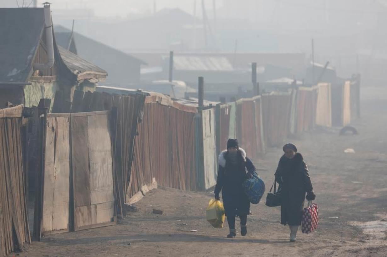 Women walk with their belongings amid smog in Sukhbaatar district of Ulaanbaatar, Mongolia January 31, 2019.
