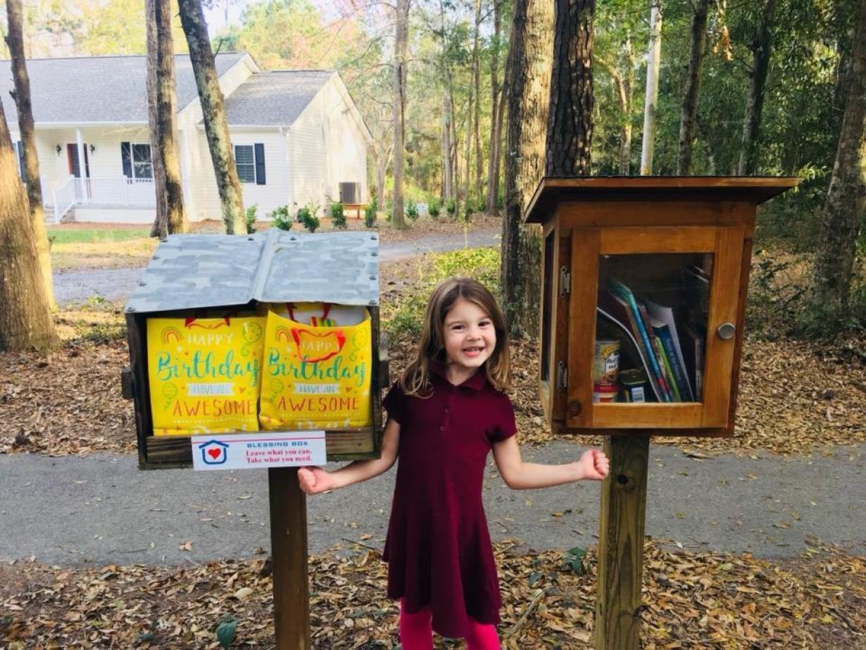 A girl poses next to a Blessing Box project in Charleston, South Carolina, in March 2019.