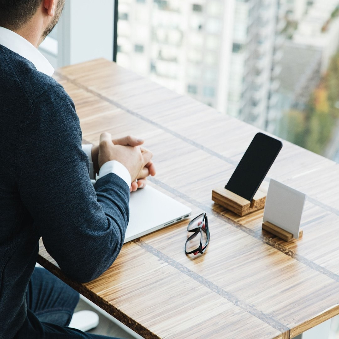 a picture of a man sitting at his desk using his mobile phone