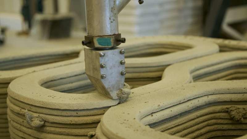 Le bras robotisé dépose des couches successives de ciment spécial à prise rapide