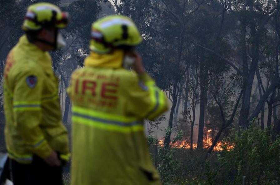 NSW Rural Fire Service and Rescue NSW personnel conduct property protection as a bushfire burns in Woodford NSW, Australia, November 8, 2019.