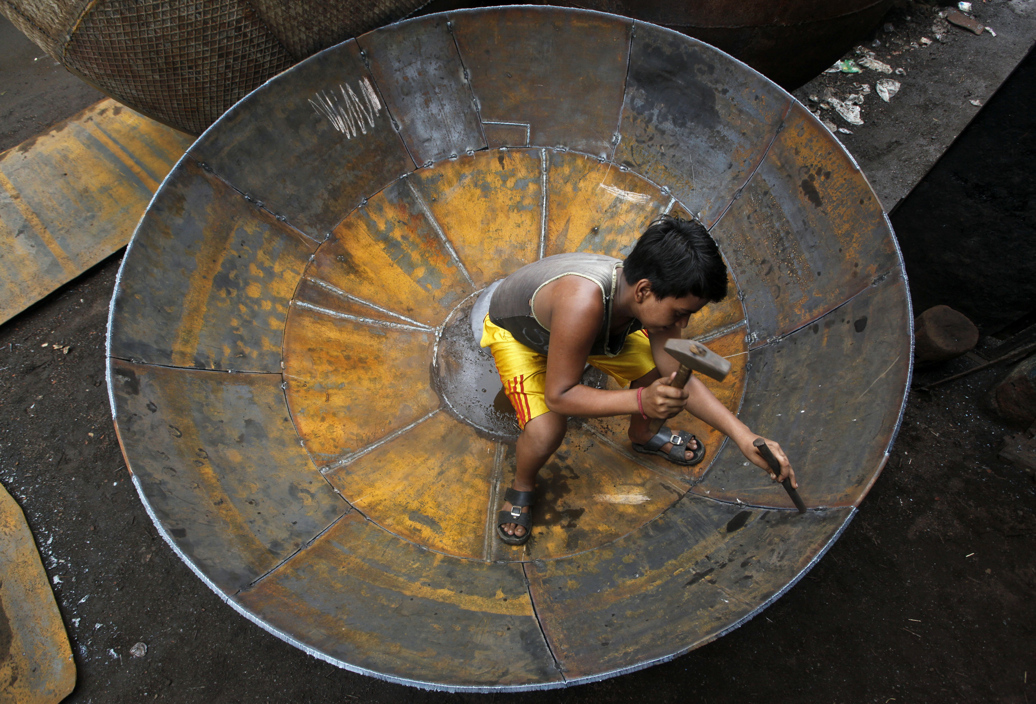 A boy checks the joints of a giant utensil at an iron utensils manufacturing unit in Kolkata July 12, 2012. India's industrial output picked up more than expected in May, bolstering the case for the central bank to keep interest rates high at its next policy meeting as a slow start to the monsoon puts pressure on inflation, especially food prices. REUTERS/Rupak De Chowdhuri (INDIA - Tags: SOCIETY BUSINESS) - GM1E87C1EUO01