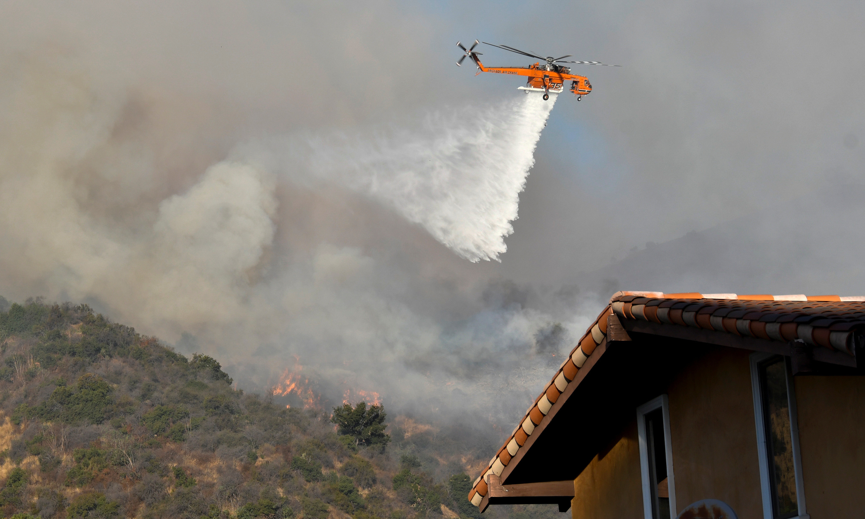 A firefighting helicopter makes a water drop on the Getty Fire as it burns in the hills of West Los Angeles, California.