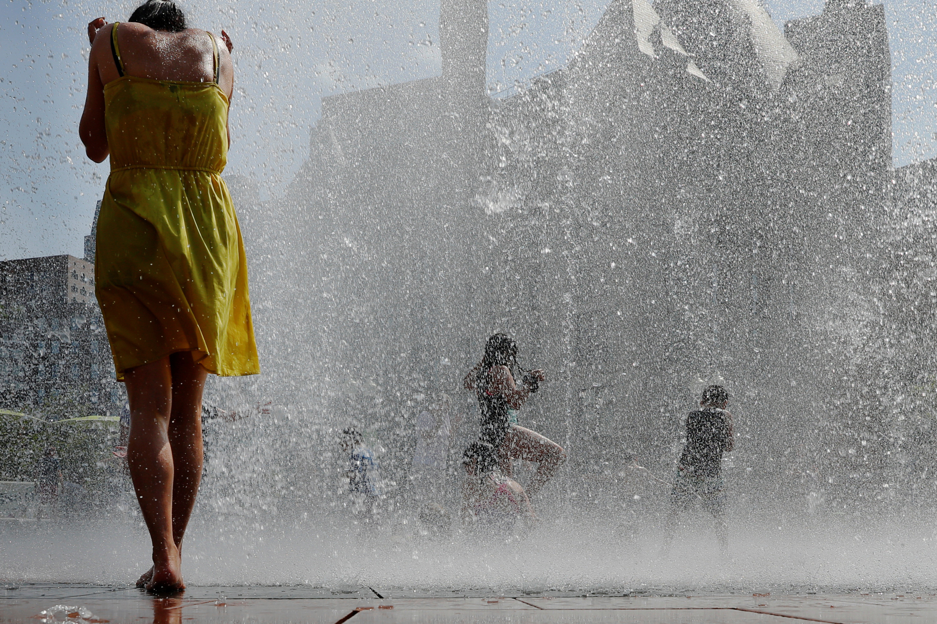 Kids and adults cool off in a fountain on the Rose Kennedy Greenway on the first day of a forecasted summer heatwave in Boston, Massachusetts, U.S., July 19, 2019.   REUTERS/Brian Snyder - RC13EDBFB540