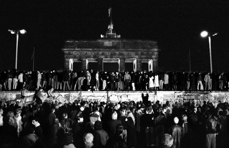East and West German citizens celebrate as they climb the Berlin wall at the Brandenburg gate after the opening of the East German border was announced in this November 9, 1989 file photo.