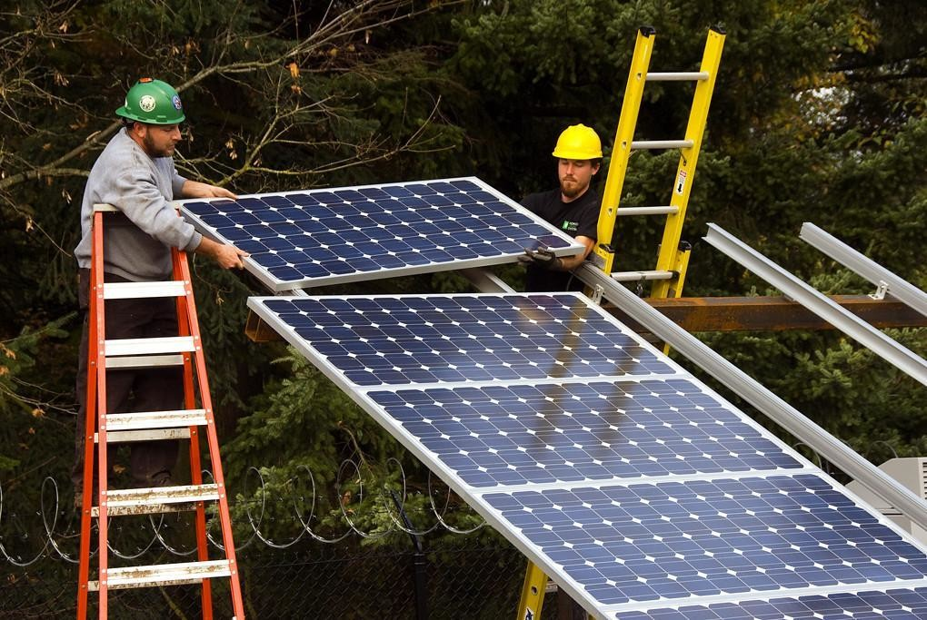 a picture of two workers installing solar panels