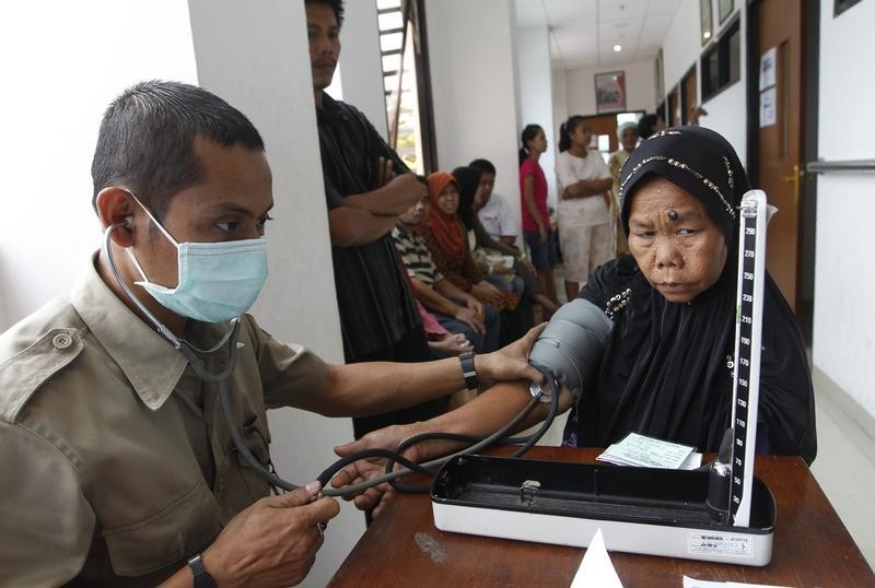 A paramedic checks a woman's blood pressure at the Tambora community health centre in Jakarta March 29, 2011. Indonesia plans to encourage the private sector to build more hospitals with a quarter of beds reserved for the poor, as it aims to boost free health care and tackle the rise of disease from stroke to AIDS, Health Minister Endang Rahayu Sedyaningsih said. REUTERS/Beawiharta (INDONESIA - Tags: HEALTH POLITICS) - RTR2KJFH
