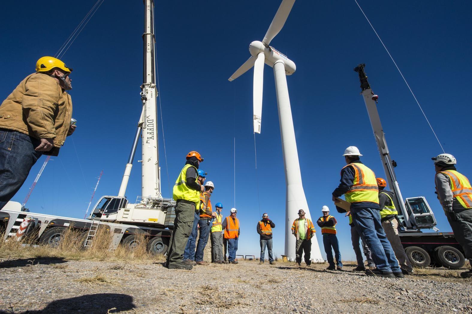 Workers install new wind turbine blades