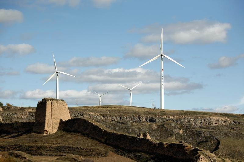 Spinning wind turbines are pictured behind part of the Great Wall of China from the border of Inner Mongolia Autonomous Region and Shanxi province October 11, 2010.