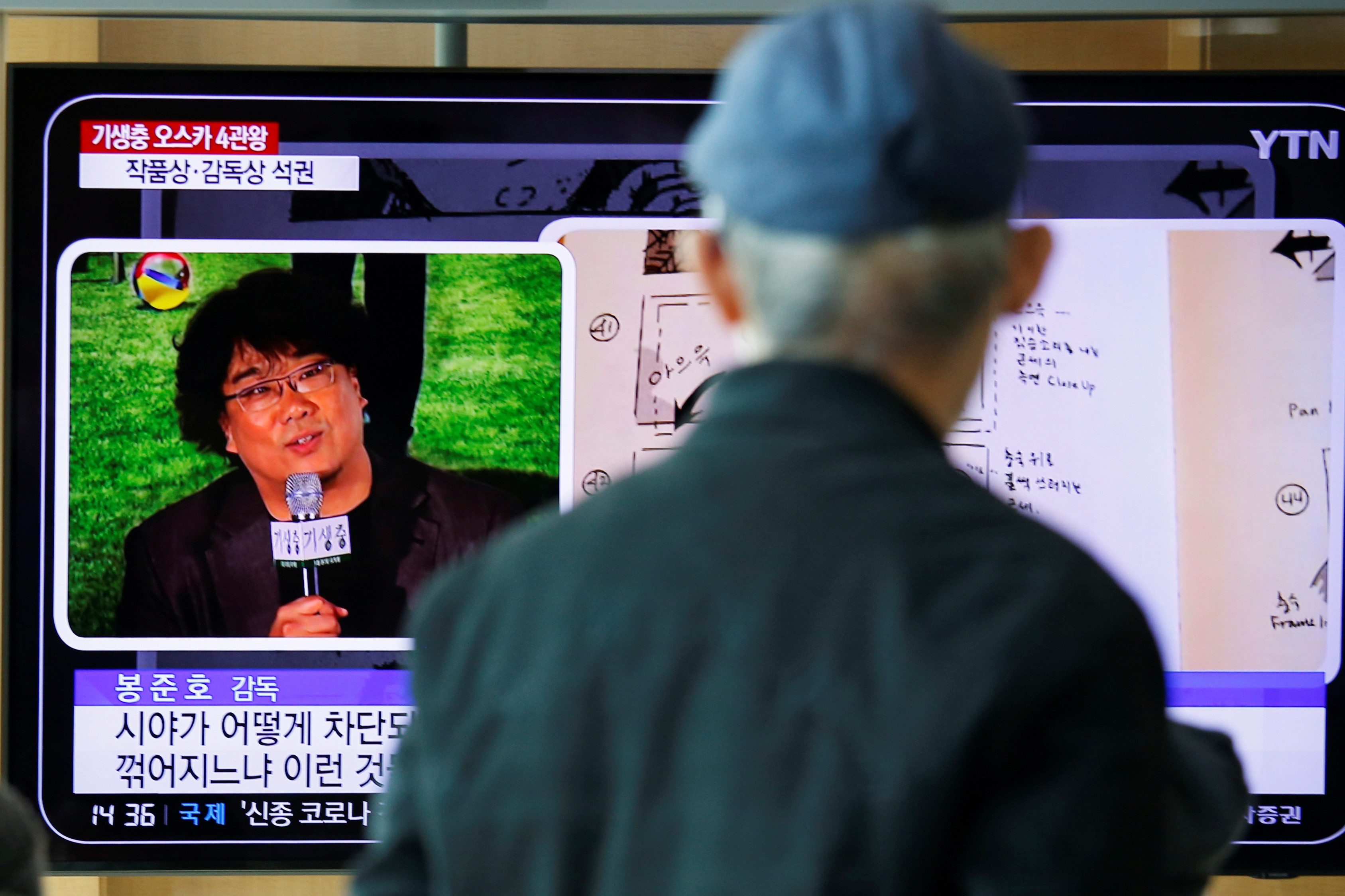 A man watches a TV broadcasting a news report onSouth Korean directorBongJoon-ho whowonfourOscarswith his film
