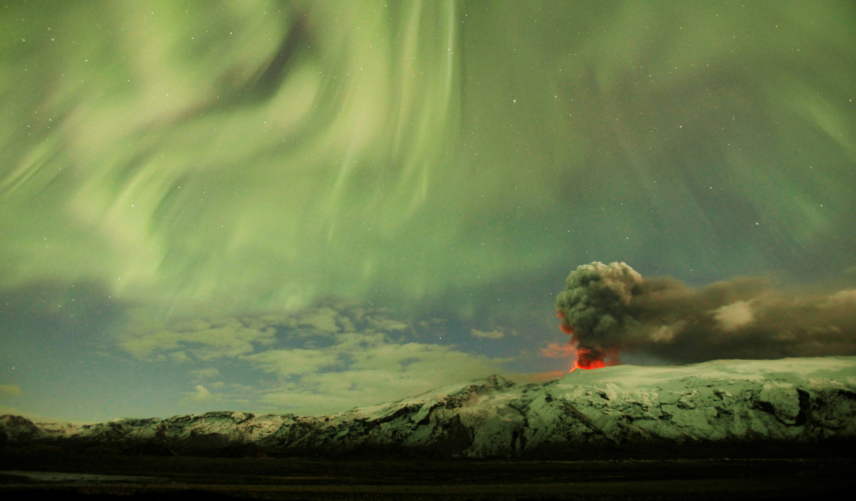 The Northern Lights are seen above the ash plume of a volcano in Eyjafjallajokull, Iceland