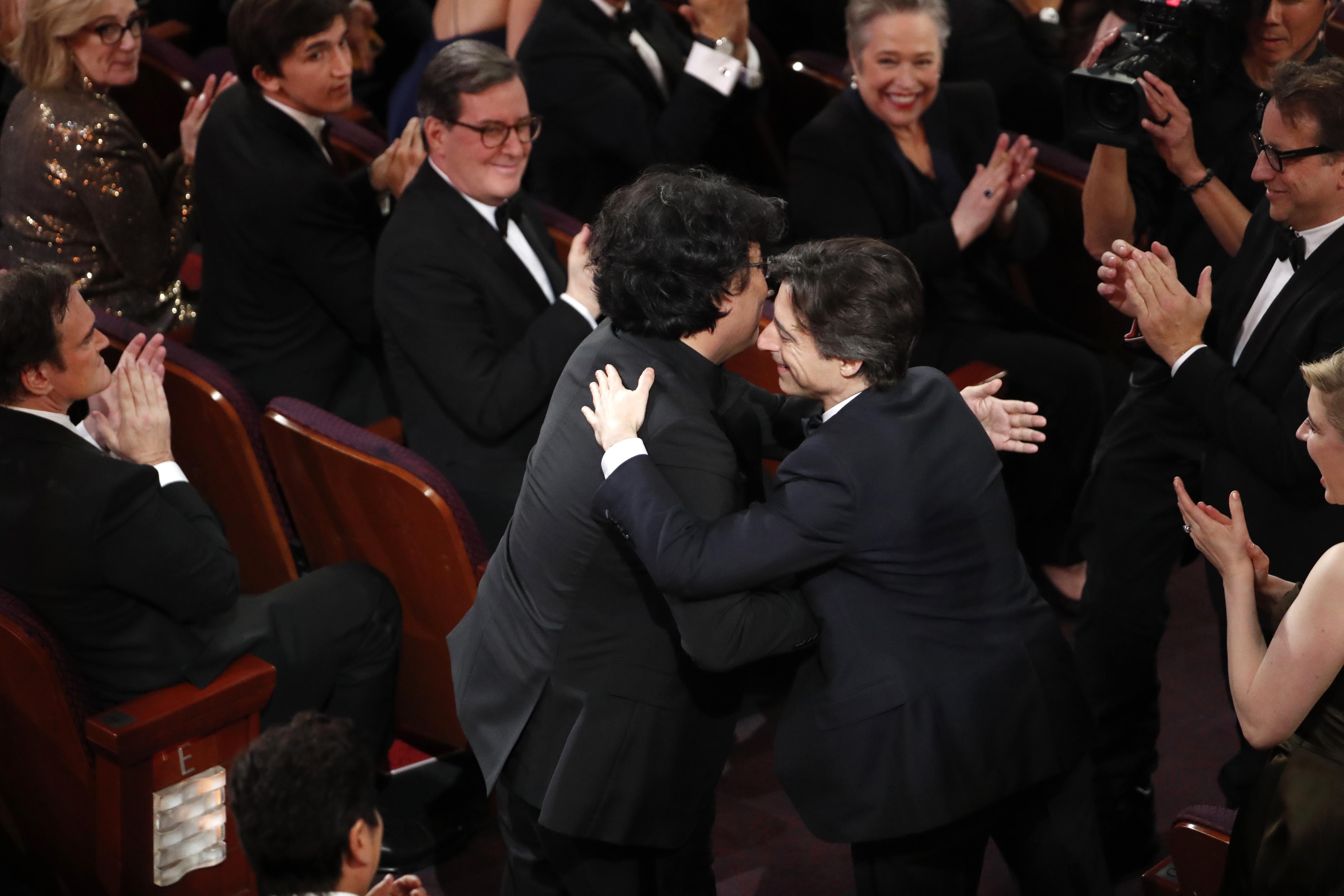 Director Bong Joon Ho (L) hugs Noah Baumbach as he wins the Oscar for Best Foreign Language Film for