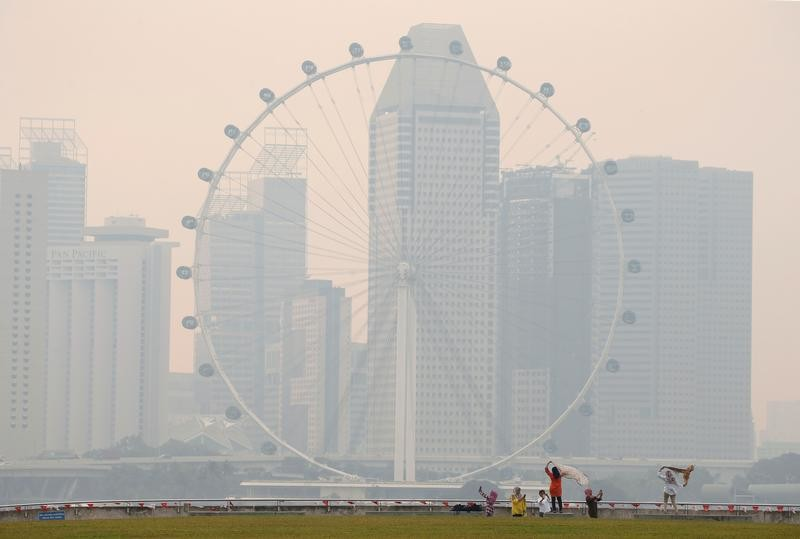 People take photos near the Singapore Flyer observatory wheel shrouded by haze August 26, 2016.