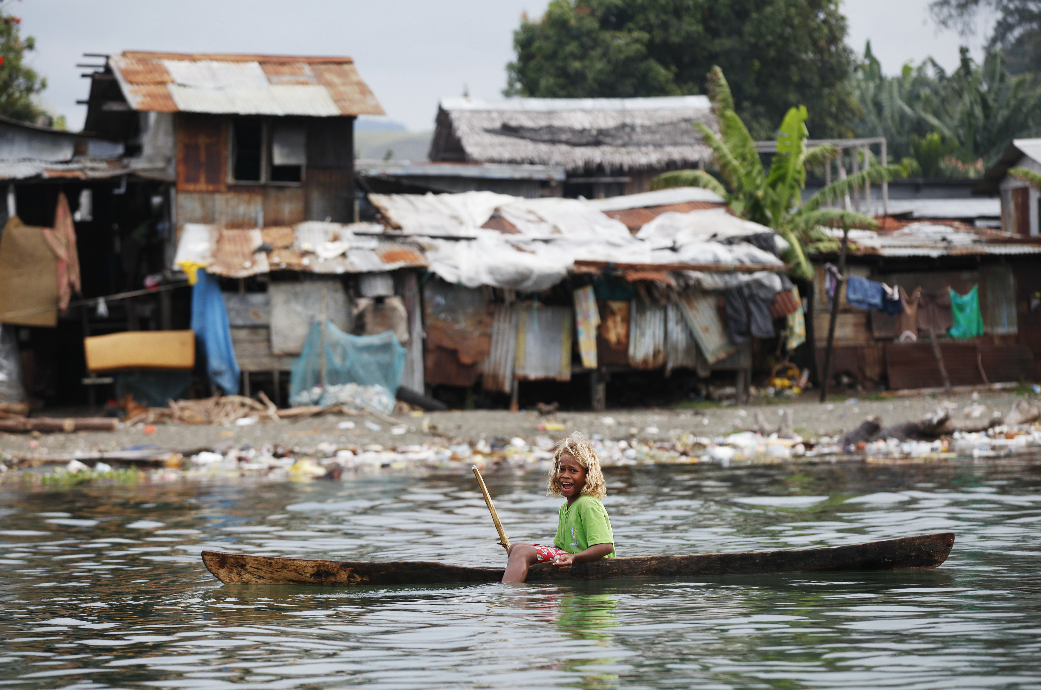 A girl fishes on her boat at a polluted beach in central Honiara September 14, 2012. The Duke and Duchess of Cambridge will visit Solomon Islands on behalf of Queen Elizabeth II to commemorate her Diamond Jubilee on September 16. REUTERS/Daniel Munoz (SOLOMON ISLANDS - Tags: SOCIETY TPX IMAGES OF THE DAY) - RTR37Z2Q