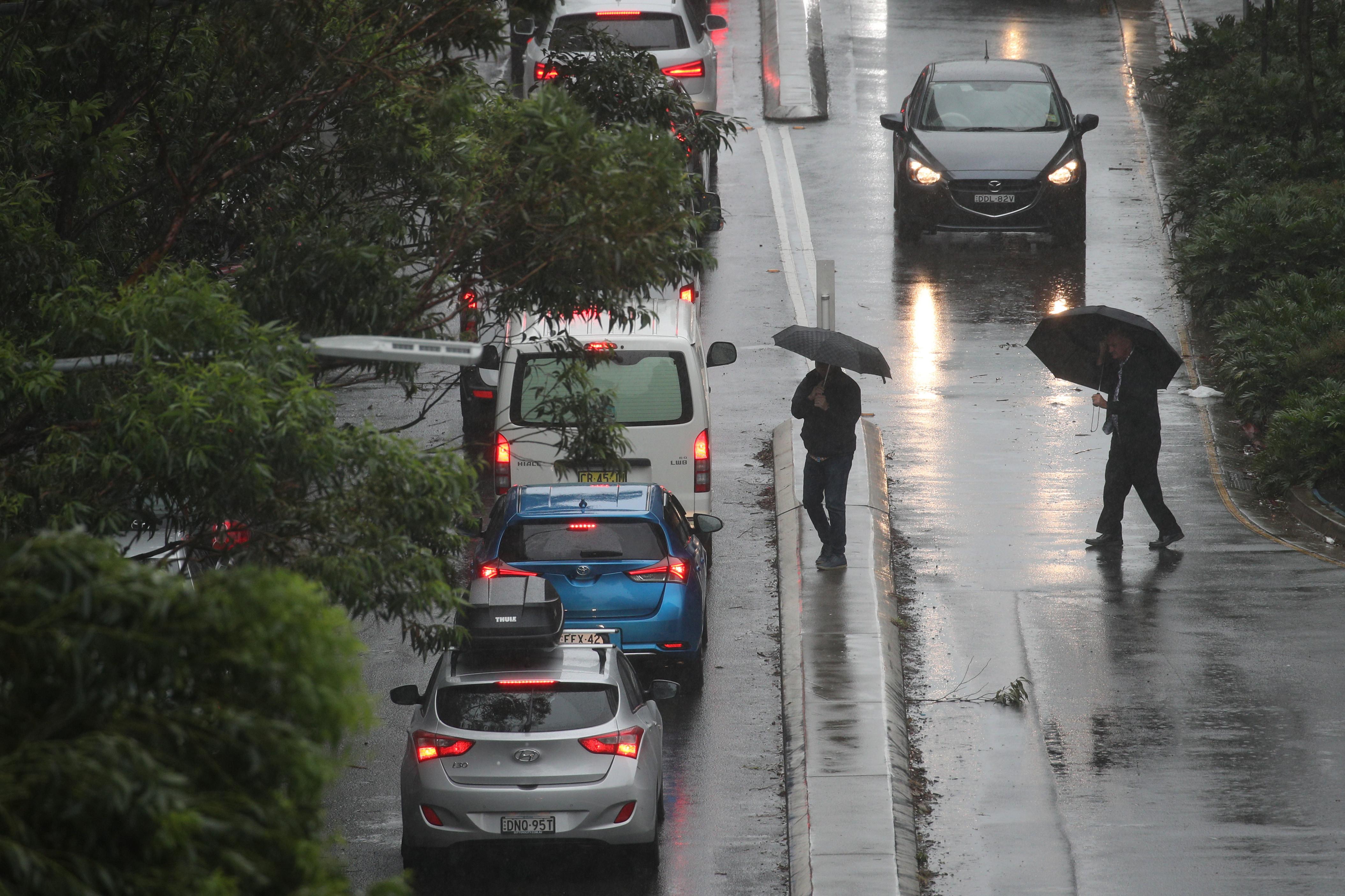 Pedestrians brave strong wind and rain in Sydney, New South Wales, Australia, February 9, 2020.  REUTERS/Loren Elliott -