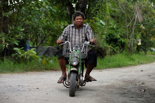 Sompot Tubcharoen, 60, rides his motorbike at his farm in Bangkok