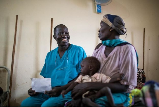 Dr Evan Atar Adaha sits with a refugee and her malnourished son in the hospital's nutrition stabilization centre.