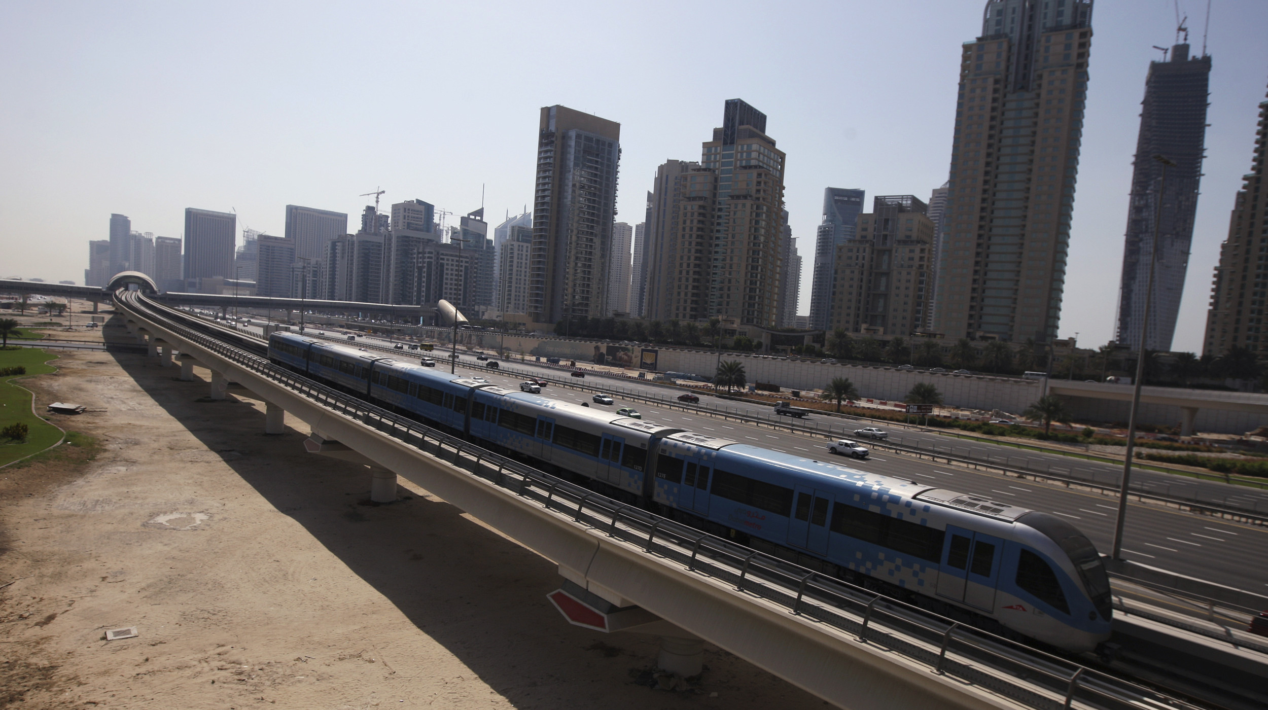 A Dubai Metro train runs past Sheikh Zayed road in Dubai September 13, 2010. State-owned conglomerate Dubai World reached a formal deal to restructure almost $25 billion of liabilities, partly easing recently heightened concerns over the Gulf emirate's debt woes. Dubai World reached an agreement with over 99 percent of its creditors by value to restructure around $24.9 billion of liabilities, the Dubai government said. REUTERS/Mosab Omar (UNITED ARAB EMIRATES - Tags: BUSINESS TRANSPORT) - RTR2IA86