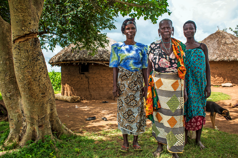 Mugosi Isombe, Veronica Nyagochera and Paulina Mukosa pose for a family portrait outside their home.