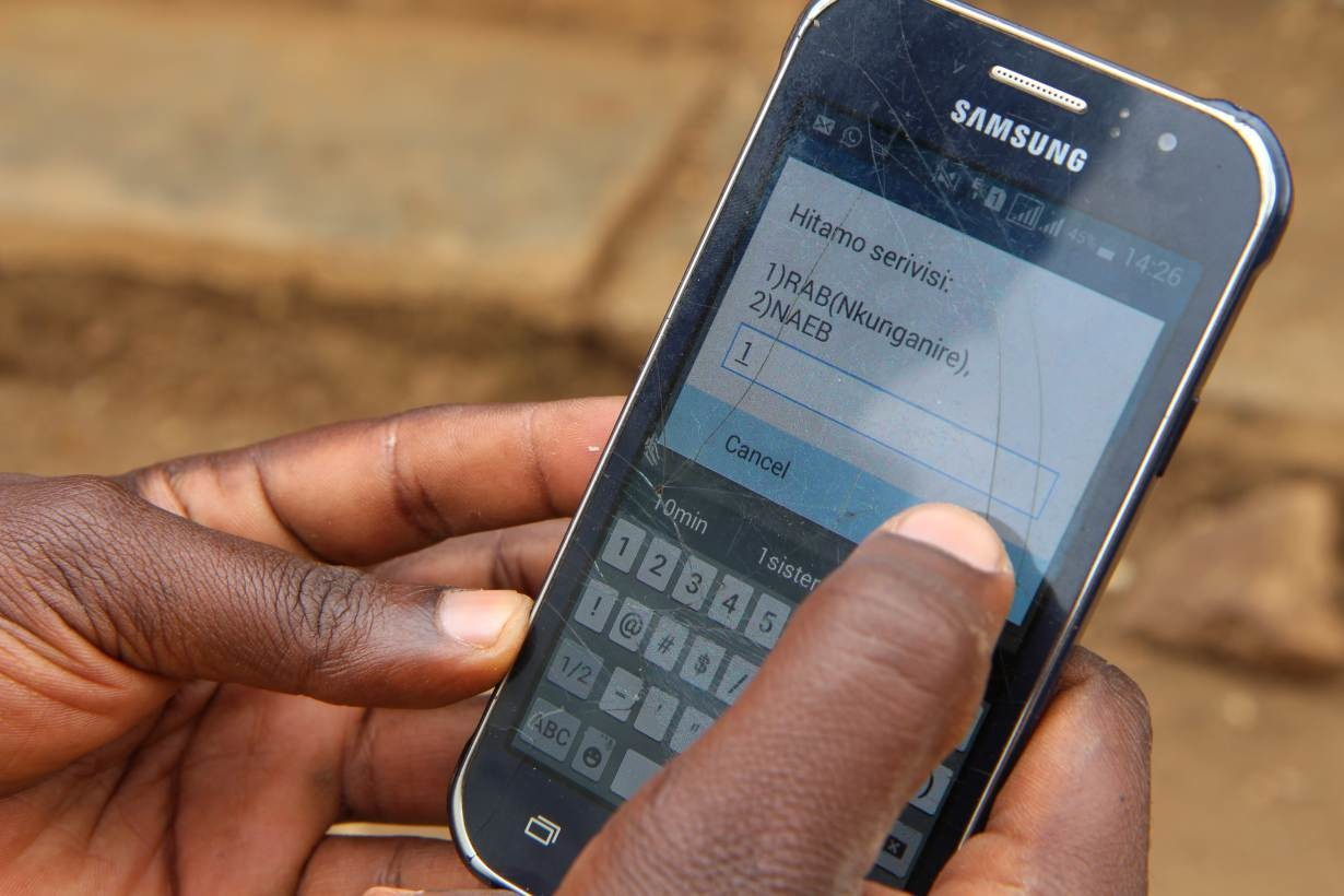 Daniel Nshimiyimana, 29, a university graduate, demonstrates how to use an app developed by the United Nations to help small scale farmers, at his farm in Rulindo district in northern Rwanda on Aug 22, 2018.