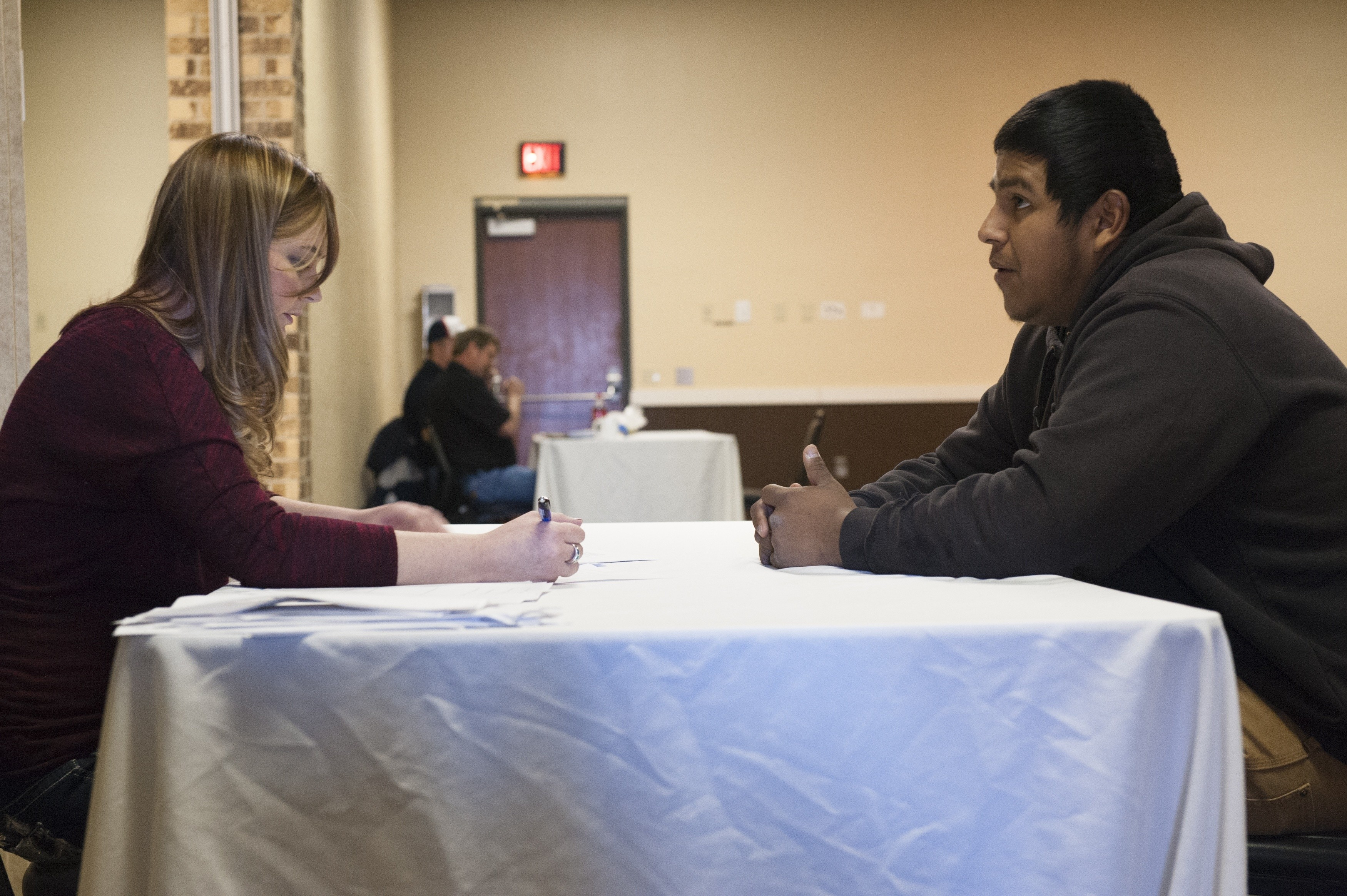 Bazileo Hernandez (R) talks to a recruiter at a hiring event hosted at a local hotel by the oilfield services company RockWater Energy Solutions in Williston, North Dakota January 22, 2015. After a week in Williston, Hernandez and his friends were still looking for steady work. Like so many before them, Terra Green, Jeff Williamson and Bazileo Hernandez came to North Dakota's oil country seeking a better life. They just came too late. Itinerant, unskilled workers could as recently as last spring show up in the No. 2 U.S. oil producing state and vie for salaries north of $100,000 per year with guaranteed housing. The steep drop in oil prices has changed that. After trying unsuccessfully for over a month to find work, the friends decided to leave Williston. REUTERS/Andrew Cullen   (UNITED STATES - Tags: BUSINESS COMMODITIES EMPLOYMENT SOCIETY) PICTURE 15 OF 28 FOR WIDER IMAGE STORY 'IN PURSUIT OF THE AMERICAN DREAM'SEARCH 'CULLEN DREAM' FOR ALL IMAGES - RTR4U0XA