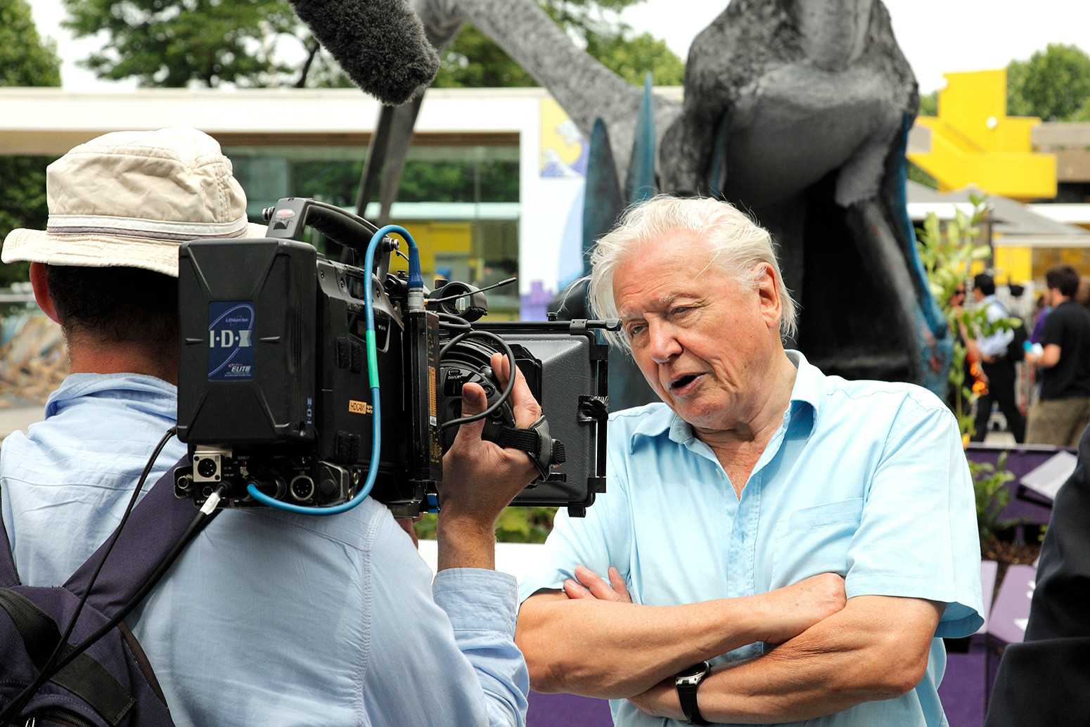 Sir David Attenborough being filmed beside an exhibition of Pterosaurs at the Southbank Centre, London.