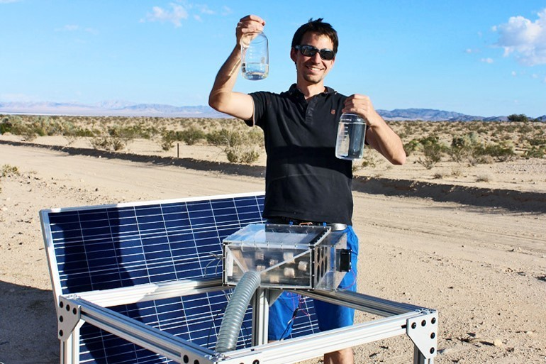 Mathieu Prévot displays water the harvester (foreground) collected in the Mojave Desert.