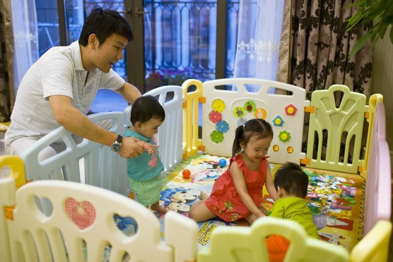 Tony Jiang poses with his three children at his house in Shanghai September 16, 2013.