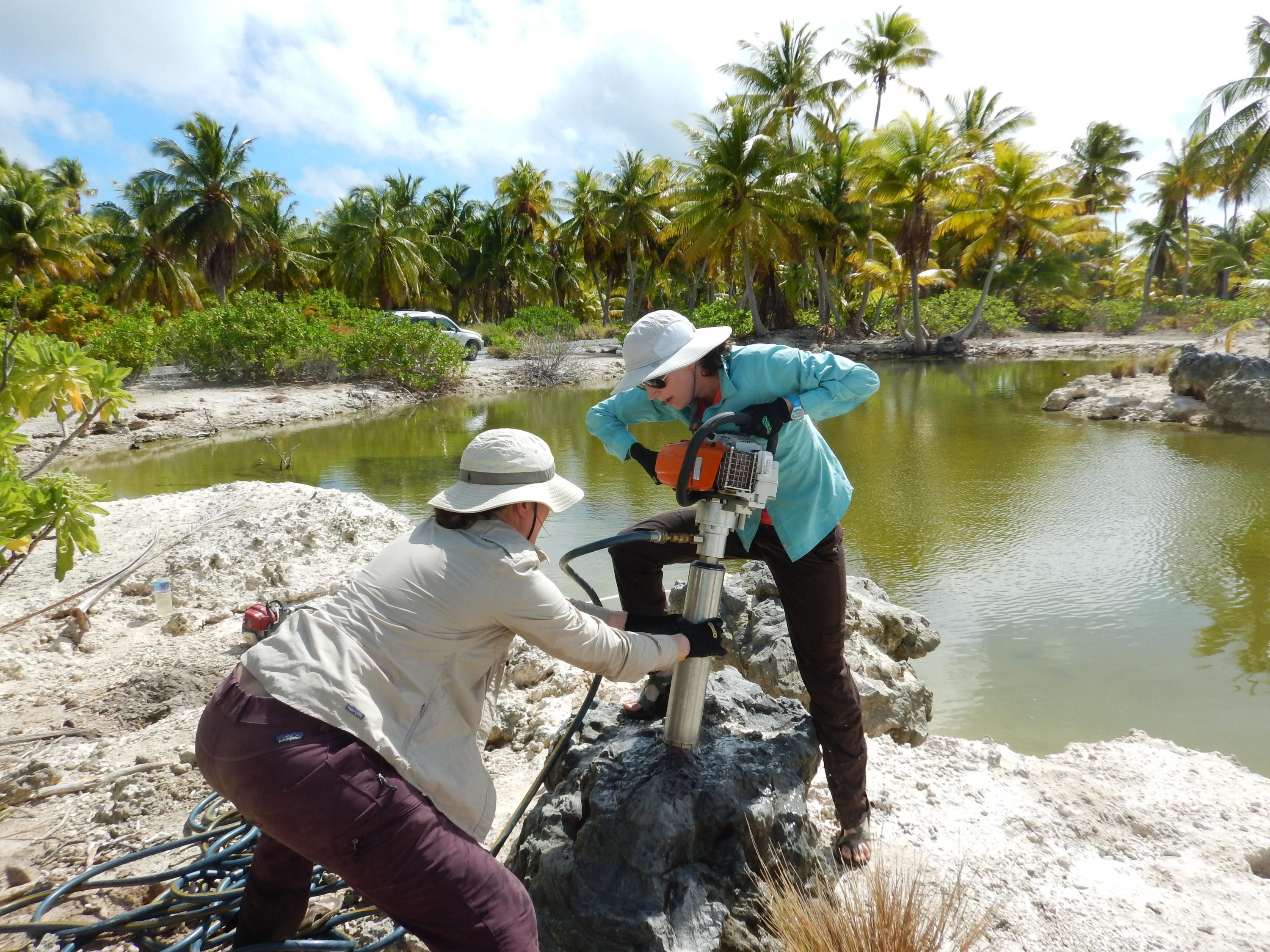Pam Grothe and Alyssa Atwood drill into a 5,000-year-old coral fossil on Kiritimati Island.