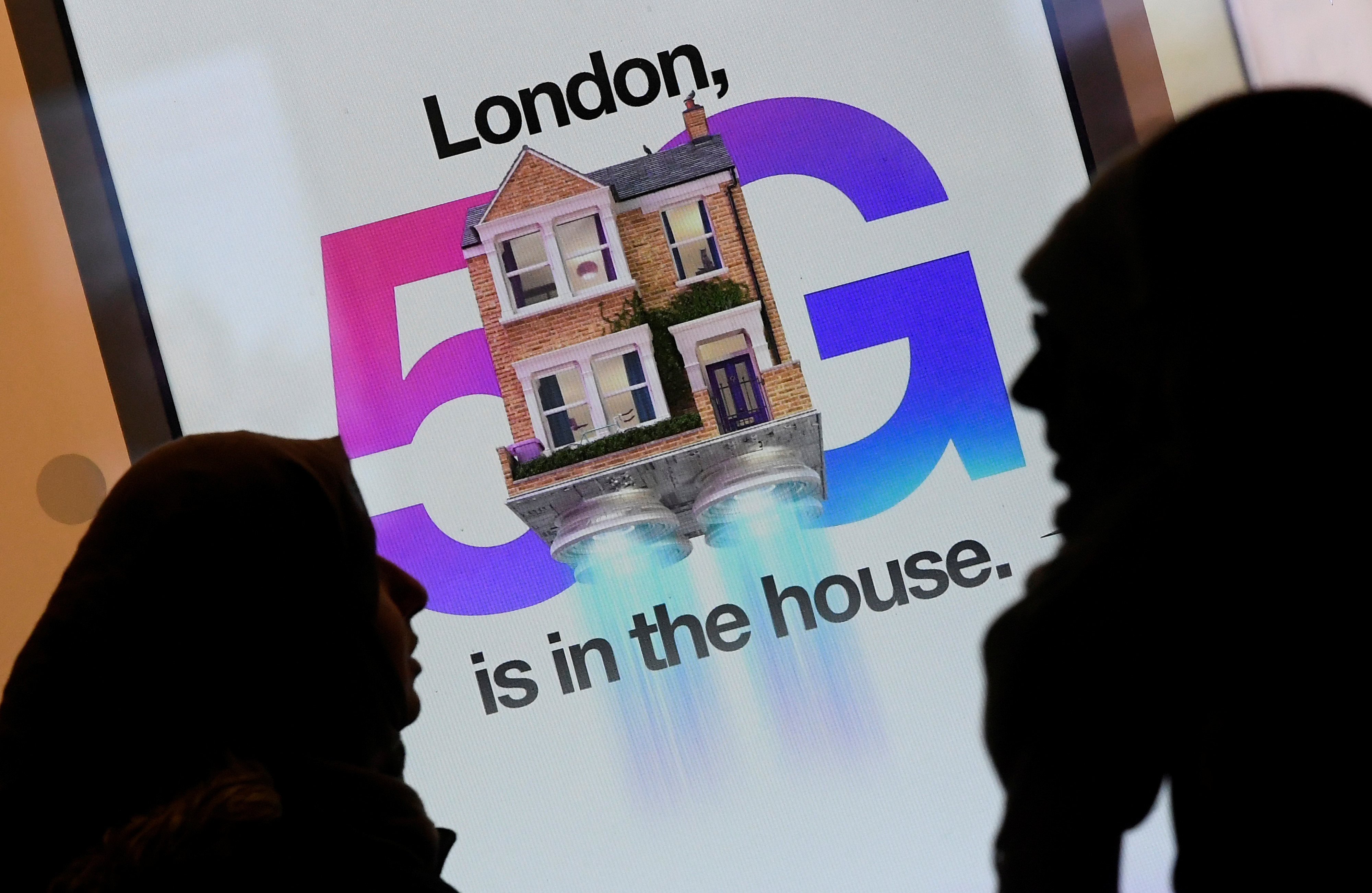 Pedestrians walk past an advertisement promoting the 5G data network at a mobile phone store in London, Britain, January 28, 2020. REUTERS/Toby Melville - RC26PE9MIDQS