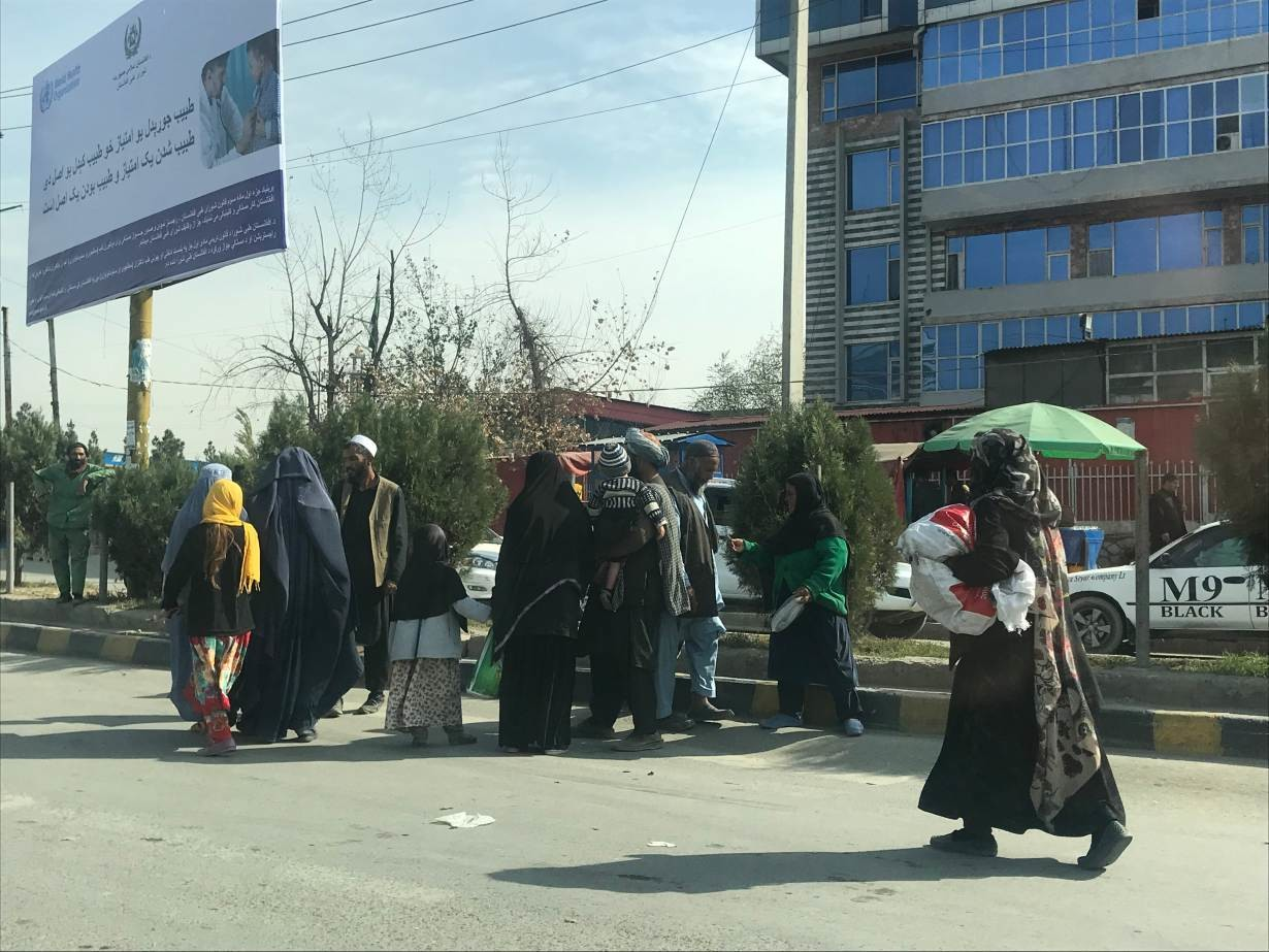 Afghan women stand by the side of the road with their families in Kabul. November 5, 2019.