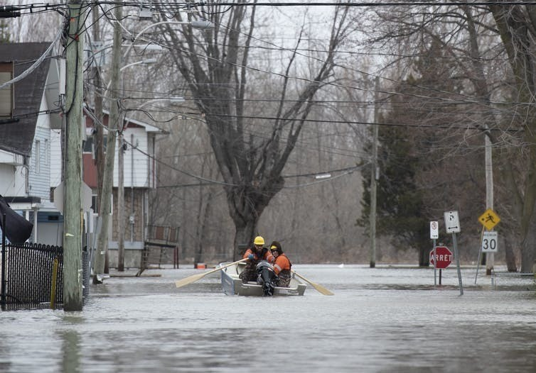 Utility workers make their way along Rue Rene in Gatineau, Que. during flooding of the Ottawa River in April 2019.